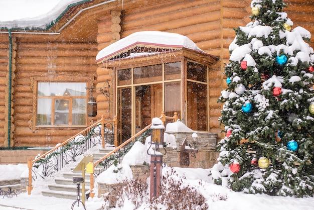 Choinka przy wejściu do drewnianego domu w śniegu Premium Zdjęcia