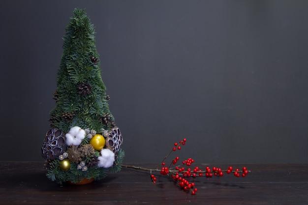 Choinka Wykonana Z Gałęzi Jodłowych I Ozdobiona Naturalnymi Materiałami Oraz Gałąź Z Czerwonymi Holly Jagodami Premium Zdjęcia