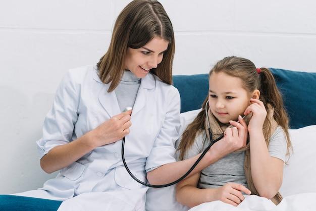Chora dziewczyna słucha kierowego rytm uśmiechnięta kobiety lekarka z stetoskopem Darmowe Zdjęcia