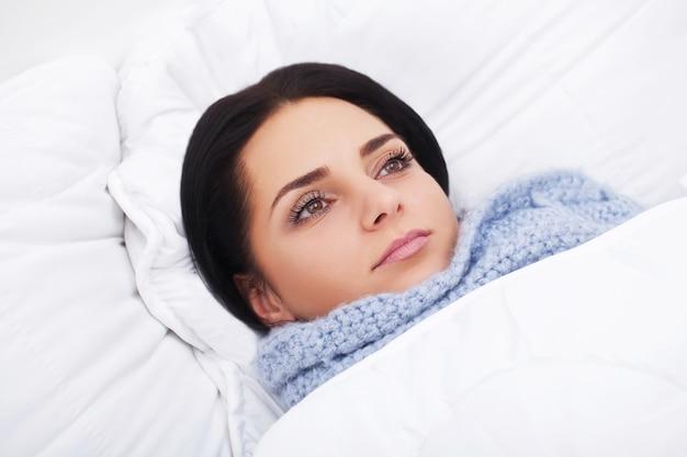 Chora kobieta. grypa. dziewczyna z zimnym leżącym pod kocem trzymającym chusteczkę Premium Zdjęcia