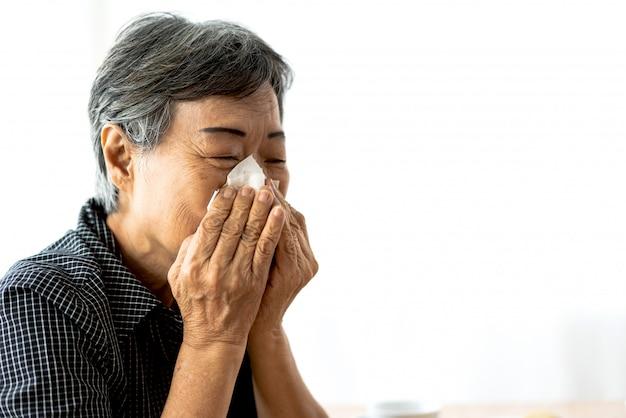 Chora Starsza Kobieta Dmucha Nos Chusteczką Papierową I Kicha Podczas Zimna. Opieka Zdrowotna I Medycyna Premium Zdjęcia