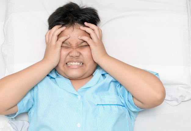 Chory gruby chłopiec cierpi na ból głowy na łóżku, Premium Zdjęcia