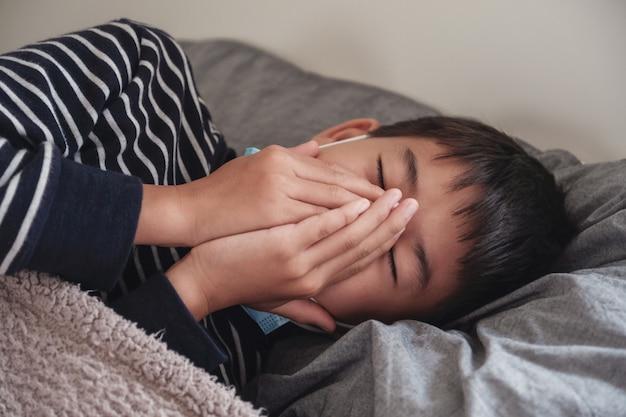 Chory Preteen Azjatycki Chłopiec Ubrany W Maskę I Kaszel W łóżku Premium Zdjęcia