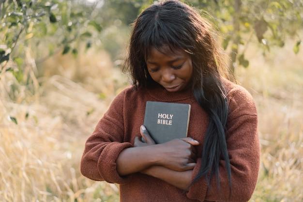 Christian Afro Dziewczyna Trzyma Biblię W Dłoniach Premium Zdjęcia