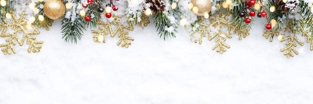 Christmas Border - Gałęzie Drzew Ze Złotymi Bombkami, Jagodami I Płatkami śniegu Na śniegu, Leżał Płasko Premium Zdjęcia