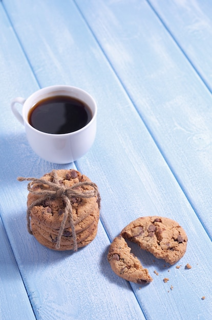 Ciasteczka Czekoladowe I Filiżankę Kawy Na Niebieskim Tle Drewnianych Premium Zdjęcia