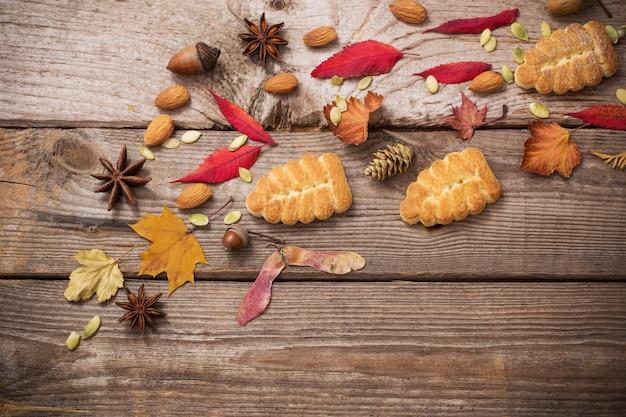 Ciasteczka I Jesienne Liście Na Podłoże Drewniane Premium Zdjęcia