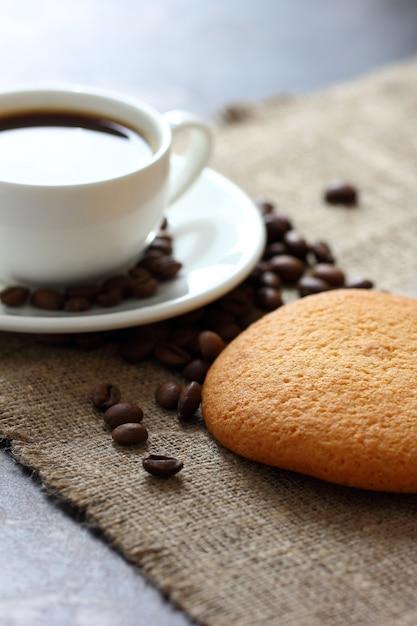 Ciasteczka Owsiane, Kubek Z Kawą I Ziarnami Kawy Rozrzucone Na Płótnie Obrus. Premium Zdjęcia