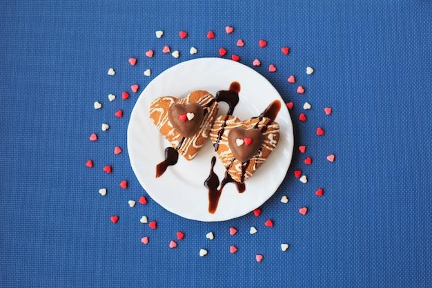 Ciasteczka W Kształcie Serca Na Małym Białym Talerzu Na Niebieskim Tle Premium Zdjęcia