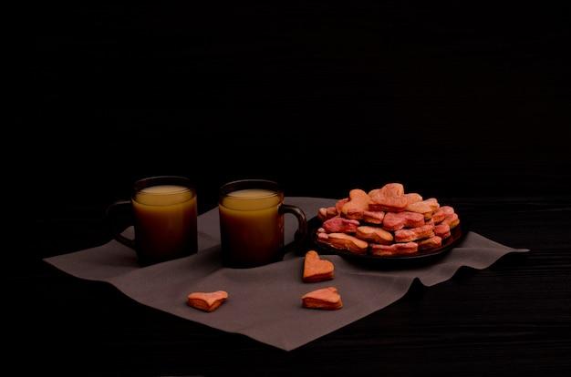 Ciasteczka z czerwonym sercem, dwa kubki kawy, walentynki Premium Zdjęcia