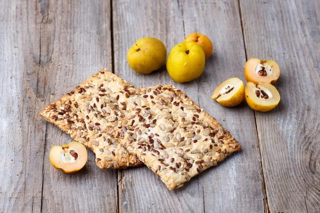 Ciastka i żółta pigwy owoc na drewnianym tle Premium Zdjęcia
