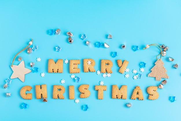 Ciastka Pisze List Wesoło Boże Narodzenia Na Błękit Powierzchni. Premium Zdjęcia