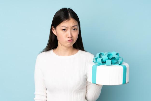 Ciasto Azjatykci Szef Kuchni Trzyma Dużego Tort Odizolowywający Na Błękit ścianie Z Smutnym Wyrażeniem Premium Zdjęcia