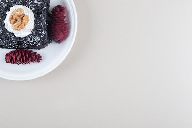 Ciasto Czekoladowe I Szyszki Sosnowe Na Talerzu Na Tle Marmuru. Darmowe Zdjęcia