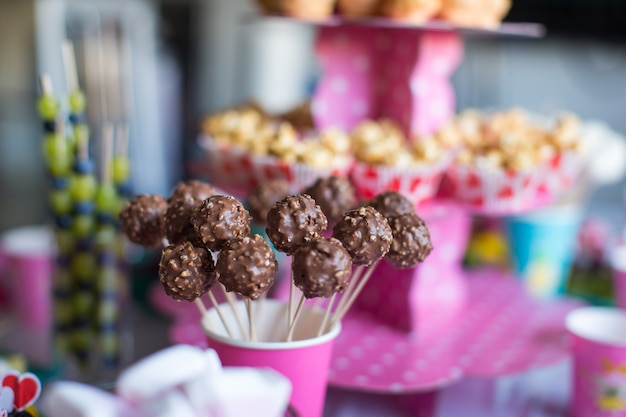 Ciasto czekoladowe wyskakuje na świątecznym stole deserowym na przyjęciu urodzinowym dla dzieci Premium Zdjęcia