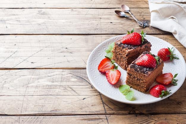 Ciasto Czekoladowe Z Truskawkami I Miętą. Drewniany Stół. Skopiuj Miejsce Premium Zdjęcia