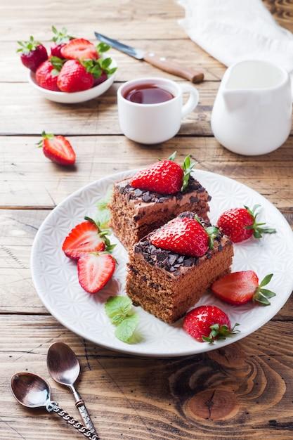 Ciasto Czekoladowe Z Truskawkami I Miętą. Drewniany Stół. Premium Zdjęcia