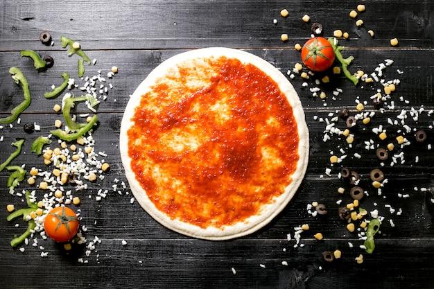 Ciasto Do Pizzy Z Sosem Pomidorowym Obok Sera Posypuje Pomidorową Papryką Kukurydzianą Darmowe Zdjęcia