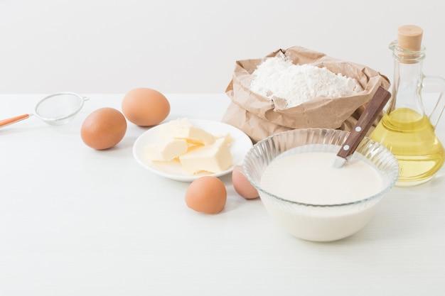 Ciasto W Szklanej Płytce I Produkty Do Jego Przygotowania Na Biało Premium Zdjęcia