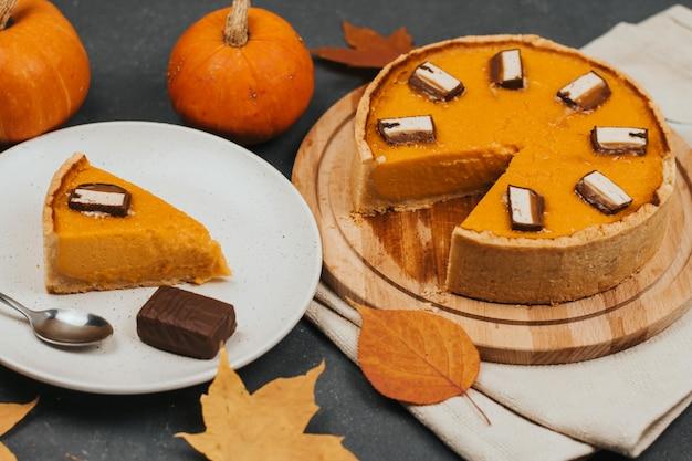 Ciasto Z Dyni Na Okrągłej Drewnianej Desce, Kawałek Ciasta Na Białym Talerzu, Jesienne Liście I Małe Dynie. Premium Zdjęcia