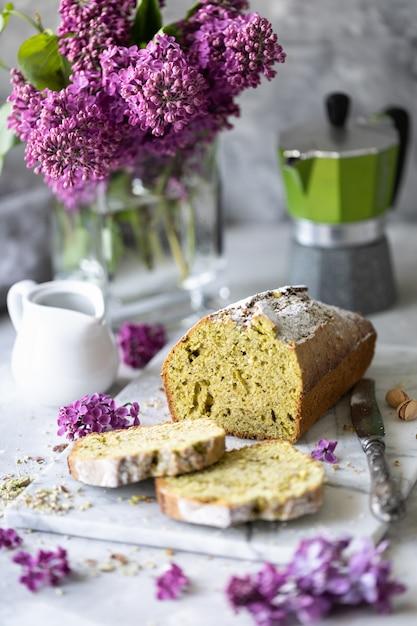 Ciasto Z Pistacjami I Szpinakiem Z Filiżanką Kawy Z Bukietem Bzu Na Stole. Kopia Przestrzeń Premium Zdjęcia