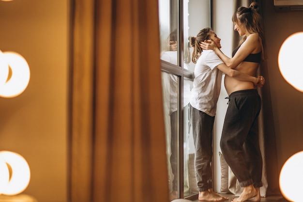 Ciąży kobiety stojącej z córką przez okno Darmowe Zdjęcia