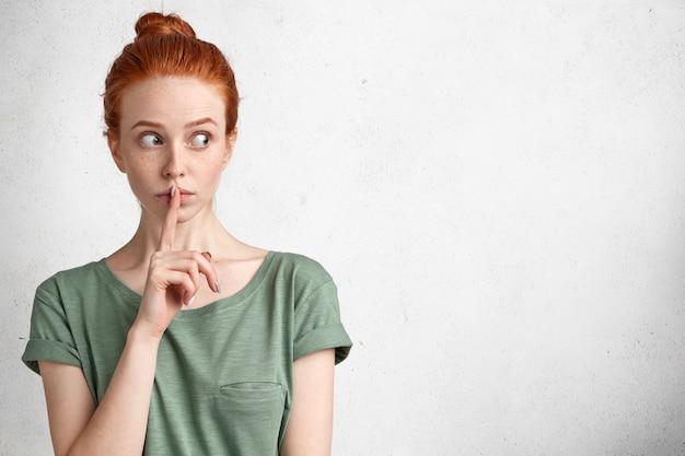Cicha Urocza Rudowłosa Kobieta O Podejrzanym Wyglądzie, Stara Się Zachować Poufne Informacje W Tajemnicy, Robi Znak Ciszy, Odizolowany Na Białym Darmowe Zdjęcia