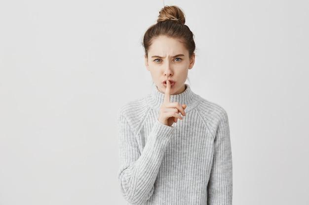 """Cicho! Headshot Caucasian Kobiety Mienia Palec Wskazujący Na Wargach. Recepcjonistka O Ciemnych Włosach Zawiązana W Kok Z Prośbą O Ciszę Mówiąc """"cii"""" Na Białej ścianie. Koncepcja Ciszy Darmowe Zdjęcia"""