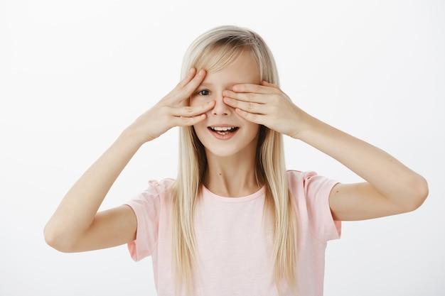 Ciekawa Córka Chce Zobaczyć, Co Ojciec Przygotował Na Urodziny. Portret Zaintrygowanej, Niecierpliwej Uroczej Dziewczyny O Pięknych Blond Włosach, Zakrywającej Oczy Dłońmi I Zerkającej Z Szerokim Uśmiechem Na Szarą ścianę Darmowe Zdjęcia