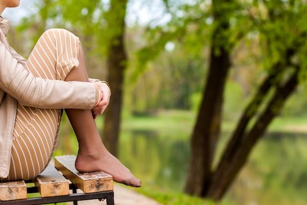Cieki Piękny Młodej Kobiety Obsiadanie Na ławce W Parku. Premium Zdjęcia