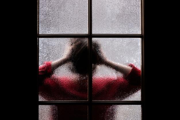 Ciemna Sylwetka Dziewczyny W Czerwieni Za Szkłem. Premium Zdjęcia