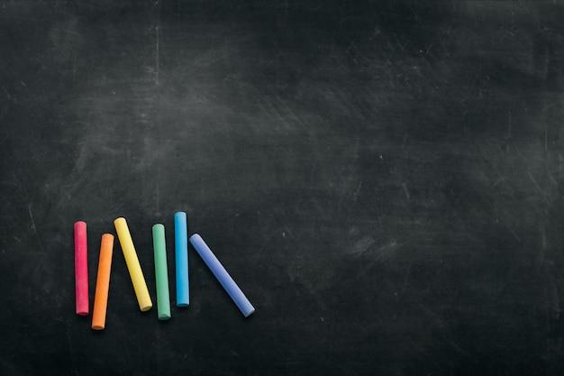 Ciemna tablica z kolorowymi kredkami do rysowania Premium Zdjęcia