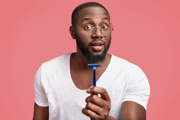 Ciemnoskóry, Brodaty Afrykański Mężczyzna Trzyma I Reklamuje Rasor Darmowe Zdjęcia