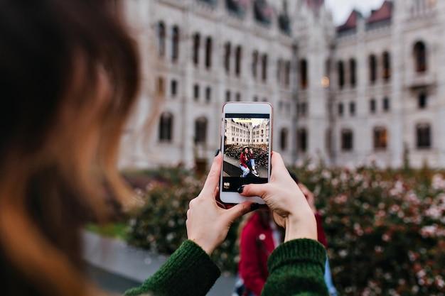 Ciemnowłosa Pani Używa Telefonu Do Robienia Zdjęcia Swojej Przyjaciółki Darmowe Zdjęcia