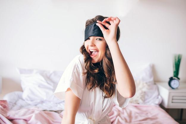 Ciemnowłosa Piękna Młoda Brunetka Budzi Się W Jej łóżku. Pozytywna Atrakcyjna Kobieta Pozuje Na Kamerze I Uśmiechu. Trzymaj Rękę Na Masce Do Spania. Sam W Sypialni. Różowa Piżama. Premium Zdjęcia