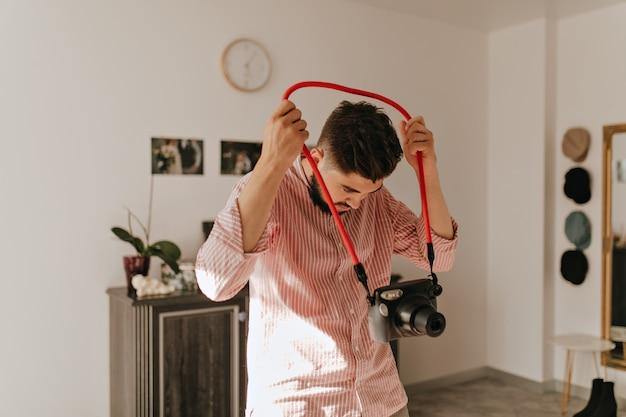 Ciemnowłosy Brodaty Mężczyzna W Lekkiej Koszuli Trzymając Aparat. Portret Faceta W Jasnym Salonie Na Tle Zdjęć ślubnych. Darmowe Zdjęcia