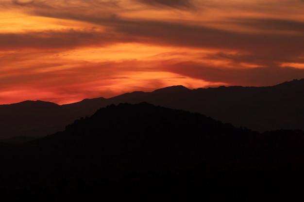 Ciemnożółte Zachmurzone Niebo Z Czarnymi Górami Darmowe Zdjęcia