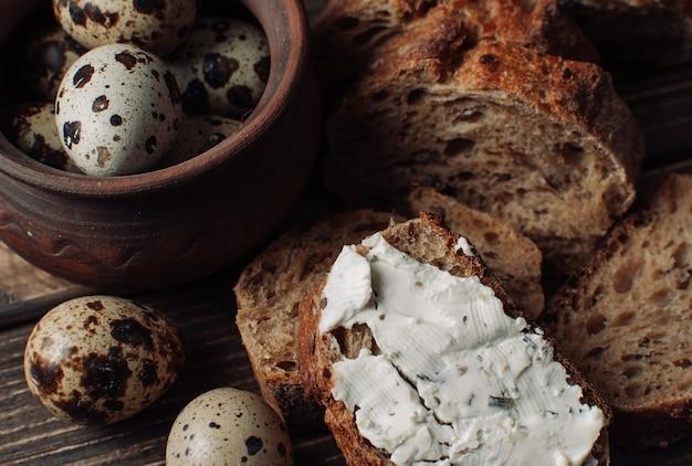Ciemny chleb gryczany rozprowadza się z twarogiem z ziołami w kawałku na drewnianym stole w pobliżu jaj przepiórczych w glinianym talerzu w rustykalnym stylu. Premium Zdjęcia