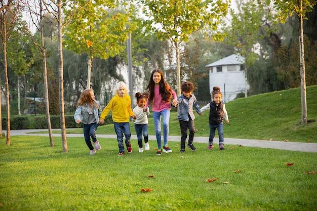 Ciepły. Międzyrasowa Grupa Dzieci, Dziewcząt I Chłopców Bawiących Się Razem W Parku W Letni Dzień. Darmowe Zdjęcia