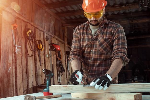 Cieśli mężczyzna notatki ołówkiem na desce zaznaczają dla cięcia, samiec ręki z ołówkowym zbliżeniem na drewnianej desce. Premium Zdjęcia