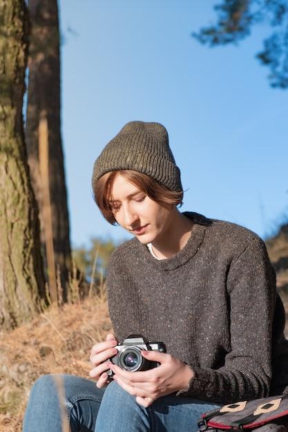 Ciesz Się Piękną Jesienną Pogodą Na świeżym Powietrzu. Młoda Kobieta Turysta Siedzi Z Aparatem Pod Sosnami W Słoneczne Popołudnie Premium Zdjęcia
