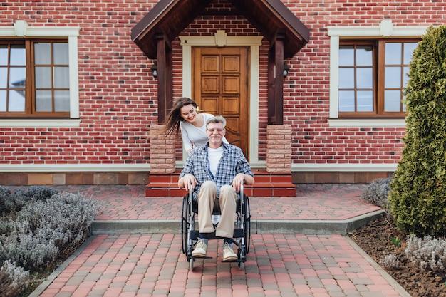 Ciesząc Się W Czasie Rodzinnym Starszy Mężczyzna Na Wózku Inwalidzkim I Uśmiechnięta Córka W Ogrodzie Premium Zdjęcia