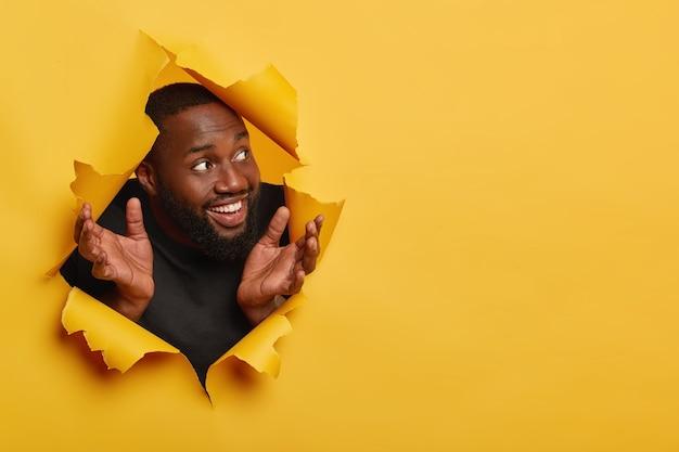 Cieszę Się, że Czarny Mężczyzna Rozkłada Dłonie Na Boki, Radośnie Patrzy Na Bok, Zauważa Coś Przyjemnego, Ma Grube Włosie, Białe Zęby, Pozuje W Rozdartej Dziurze Na żółtym Tle Darmowe Zdjęcia