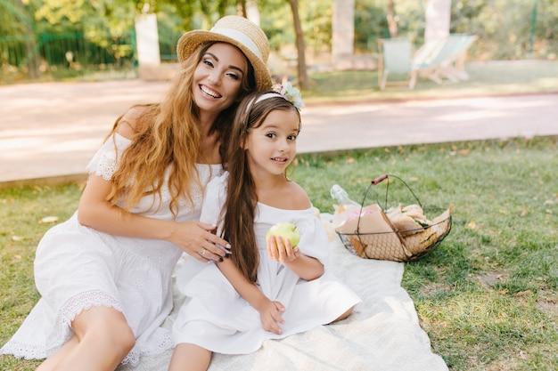 Cieszę Się, że Młoda Kobieta W Eleganckim Stroju Delikatnie Obejmuje Dziewczynę, Z Apetytem Je Zielone Jabłko. Zewnątrz Portret Szczęśliwej Rodziny Obiad W Parku I żartuje. Darmowe Zdjęcia