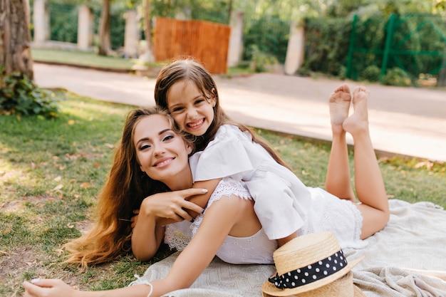 Cieszę Się, że Młoda Kobieta Z Blaskiem Makijażem Chłodzi Na Koc Z Nogami I Uśmiecha Się. śmiejąca Się Opalona Dziewczyna Leżąca Na Plecach Matki Darmowe Zdjęcia