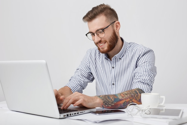 Cieszę Się, że Modny Mężczyzna Z Uśmiechem Pisze Na Zwykłym Laptopie, Sprawdza Pocztę Elektroniczną Lub Wiadomości Online Darmowe Zdjęcia