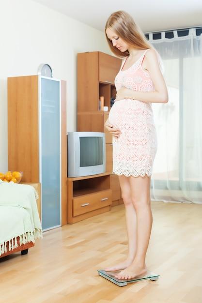 Ciężarna kobieta stojąca na wadze łazienkowej Darmowe Zdjęcia