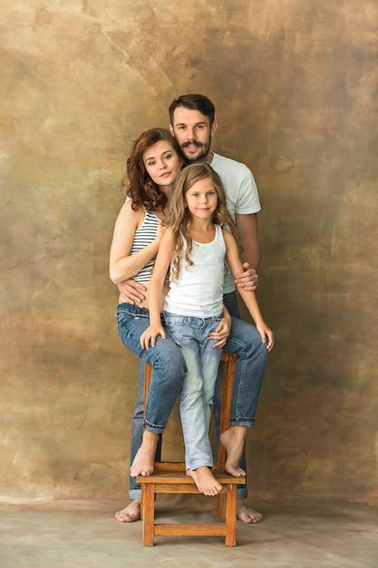 Ciężarna Matka Z Nastoletnią Córką I Mężem. Rodzinny Pracowniany Portret Nad Brown Tłem Darmowe Zdjęcia