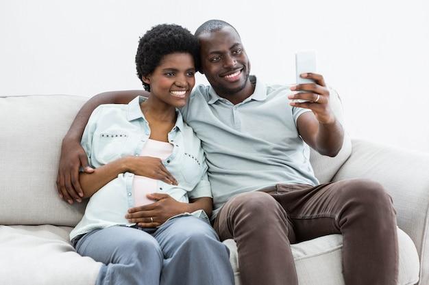 Ciężarna Para Bierze Selfie Na Telefonie Komórkowym W Domu Premium Zdjęcia