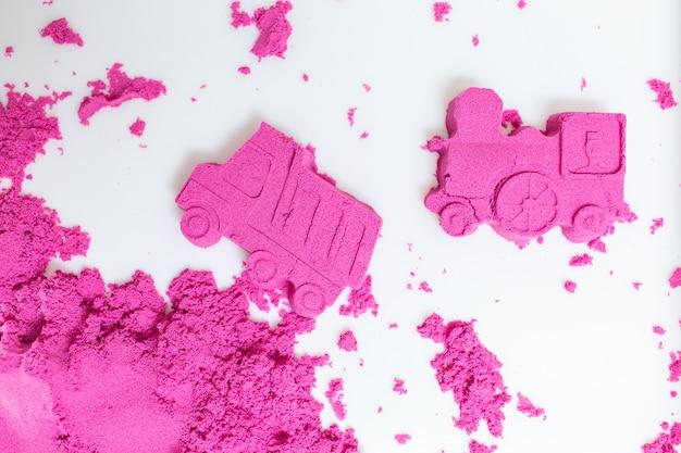 Ciężarówka i pociąg robić z różowym kinetycznym piaskiem na białym tle. Premium Zdjęcia